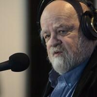 Gros plan de Serge Bouchard devant le micro, avec des écouteurs.