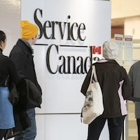 Des gens font la file devant un bureau de Service Canada.