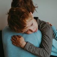 Une personne porte dans ses bras un enfant triste.