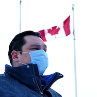 Eric Redhead est dehors devant un drapeau du Canada. Il est vêtu d'un manteau et porte un masque.