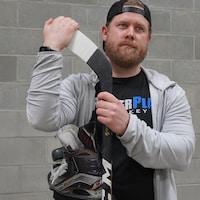 Un homme avec une paire de patin et bâton de hockey dans les mains.