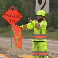 Une femme qui est sur un chantier routier donne des indications aux automobilistes.