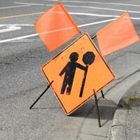 Dessin d'un signaleur routier sur un panneau de circulation, sur le sol