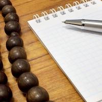 Un collier religieux sur un bureau, près d'un carnet de note et d'un stylo.