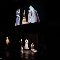 Capture d'écran d'une scène de la pièce avec trois femmes portant des robes de mariées.