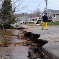 Un homme marche sur une route endommagée par les inondations au Nouveau-Brunswick.