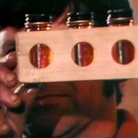 Un homme compare des fioles de sirop d'érable.