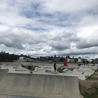 Quatre jeunes font du skate dans le parc ce skate lors d'une journée ennuagée.