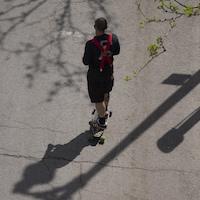 Un jeune homme se promène en planche à roulettes sur une chaussée craquelée.
