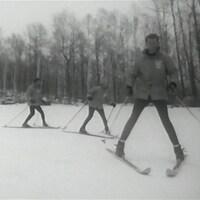 Trois skieurs se suivant en file sur une piste, les skis en pointe de tarte.