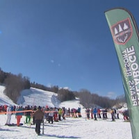 De nombreux skieurs attendent les uns derrière les autres et on aperçoit au loin les pistes de descentes.
