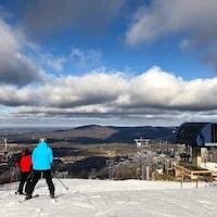 Deux skieurs au sommet de la montagne à Bromont regardent à l'horizon.