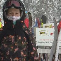 Une jeune femme en habit d'hiver porte un masque qui couvre sa bouche et son nez. Elle se tient debout à l'extérieur avec ses skis en main.