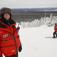 Un homme au sommet d'une piste de ski.