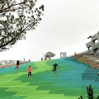 Des skieurs sur la piste synthétique aux multiples teintes de vert de la CopenHill.