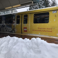 Un banc de neige en premier plan devant un wagon de skytrain couvert d'une publicité de Lego.