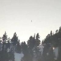 Une personne marchant sur une sangle tendue entre deux pics montagneux.