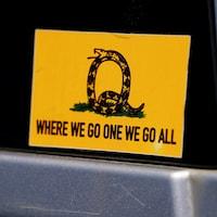 Un autocollant de QAnon sur lequel on peut lire le slogan utilisé par l'organisation : « Quand un de nous y va, nous y allons tous. »