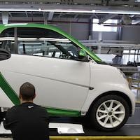 Un homme répare une voiture électrique.