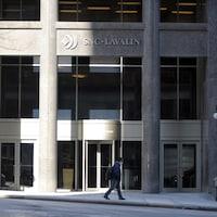Un homme marche devant le siège social de SNC-Lavalin, à Montréal.