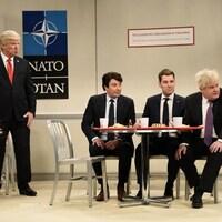 Alec Baldwin est debout et les autres sont assis autour d'une table.