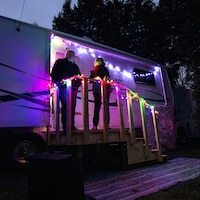 Deux personnes devant leur véhicule récréatif décoré de lumières.