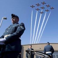 Des avions volent au-dessus des têtes de nombreux militaires.