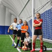 Cinq joueuses de soccer du club Greater Sudbury Soccer Club prennent la pose devant un filet de but de soccer.