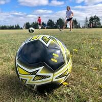Un ballon de soccer en avant plan avec des jeunes joueuses en arrière plan