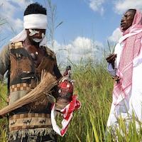Deux hommes en tenue traditionnelles dans les champs portent des objets de rituels en main.