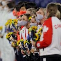 Les joueuses de l'équipe féminine de softball du Canada se tiennent en rangée. Chacune a sa médaille autour du cou et un bouquet de fleurs dans ses mains.