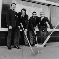 À l'extérieur, sur le trottoir devant l'édifice Radio-Canada, l'analyste sportif Gilles Tremblay est debout tandis qu'à côté de lui, les commentateurs Richard Garneau, Lionel Duval et René Lecavalier sont penchés, déposant un bâton de hockey devant eux sur le trottoir.