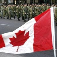 Des militaires portant l'uniforme des Forces armées canadiennes paradant à proximité d'un drapeau du Canada.