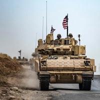 Deux soldats dans un char d'assaut avec un drapeau américain.