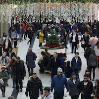 Une foule dans un centre commercial décoré pour Noël.