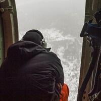 Un homme observe une forêt de haut, à bord d'un avion.