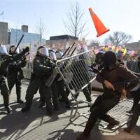 Des manifestants lancent un cône et poussent une clôture vers des policiers.