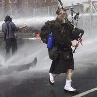 Un joueur de cornemuse brave un jet d'eau de la police lors du Sommet de Québec, en 2001.