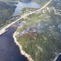 Tadoussac vu des airs. On peut voir de la fumée sortir de la forêt.