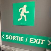 Des panneaux indiquent une sortie de secours.