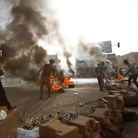Plusieurs manifestants, dont une femme, construisent un mur de briques ou alimentent l'incendie de pneus.