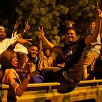 Plusieurs personnes font des signes de paix avec leurs doigts à l'arrière d'une camionnette dans la nuit à Khartoum.