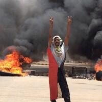 Un homme portant le drapeau soudanais comme une cape fait le signe de la victoire devant des débris en feu.