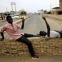 Deux manifestants font le V de la victoire sur une barricade de fortune en briques. La rue bloquée est pratiquement déserte.