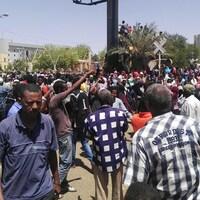Une foule est massée devant des immeubles.