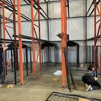 Deux personnes installent des cages.