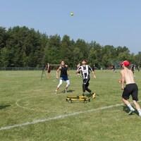 Des joueurs lors d'une partie de spikeball qui consiste à faire rebondir une ball sur un petit trampoline situé au centre des participants
