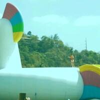 Un jeune s'apprête a glisser le long de la queue d'une énorme licorne gonflable placée sur un point d'eau.