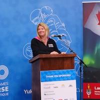 Jeane Lassen derrière un podium avec en fond l'affiche des Jeux d'hiver de l'arctique 2020.