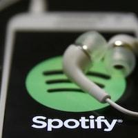 Le logo de l'application Spotify apparaît sur l'écran d'un téléphone intelligent. Des écouteurs sont déposés sur le téléphone.